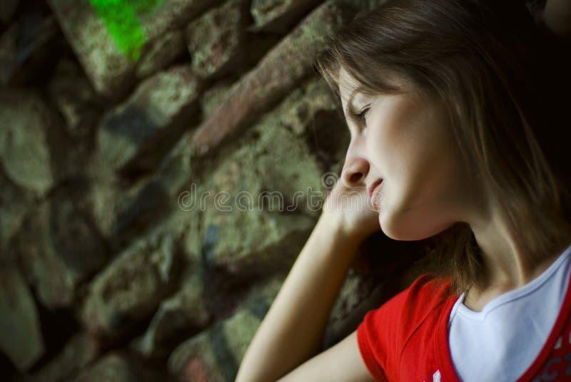 Femme se penchant sur le mur photos stock