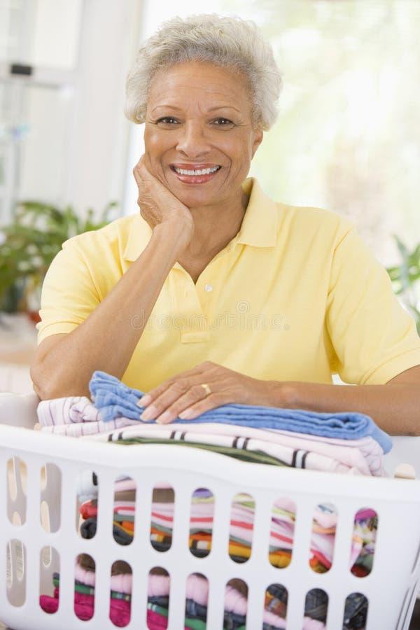Femme se penchant sur le panier de lavage images libres de droits
