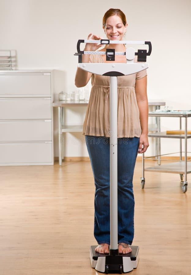 Femme se pesant dans le bureau de docteur photo libre de droits