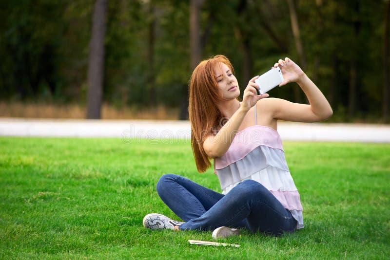 Femme se photographiant en parc images libres de droits