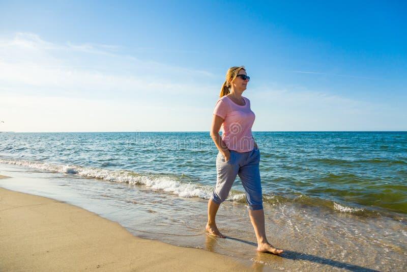 Femme se réveillant sur la plage images libres de droits