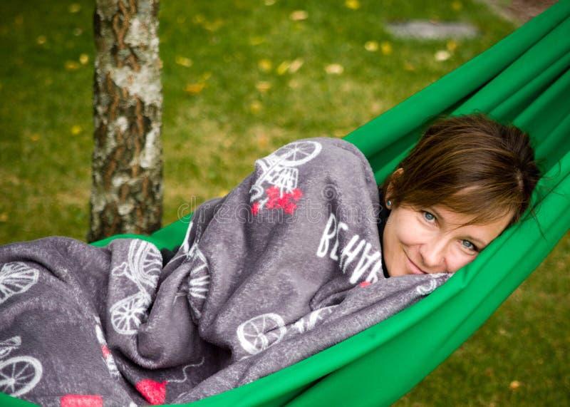 Femme se reposant dans l'hamac vert photos stock