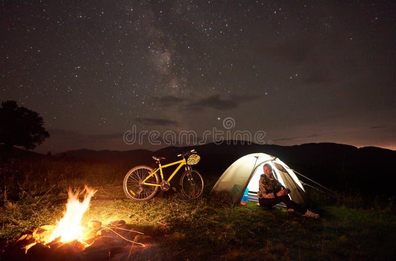 Femme se reposant la nuit campant près du feu de camp, tente de touristes, bicyclette sous le ciel de soirée complètement des éto photos libres de droits