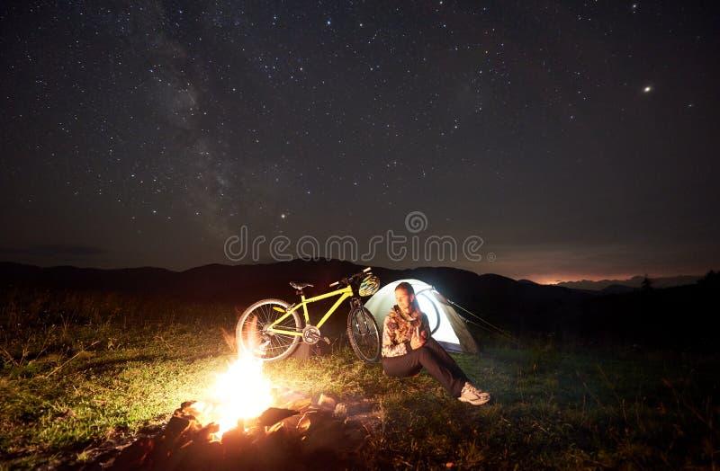 Femme se reposant la nuit campant pr?s du feu de camp, tente de touristes, bicyclette sous le ciel de soir?e compl?tement des ?to photo libre de droits