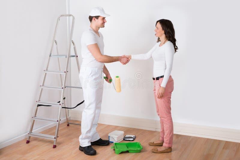 Femme se serrant la main au peintre With Paint Roller à la maison photo libre de droits