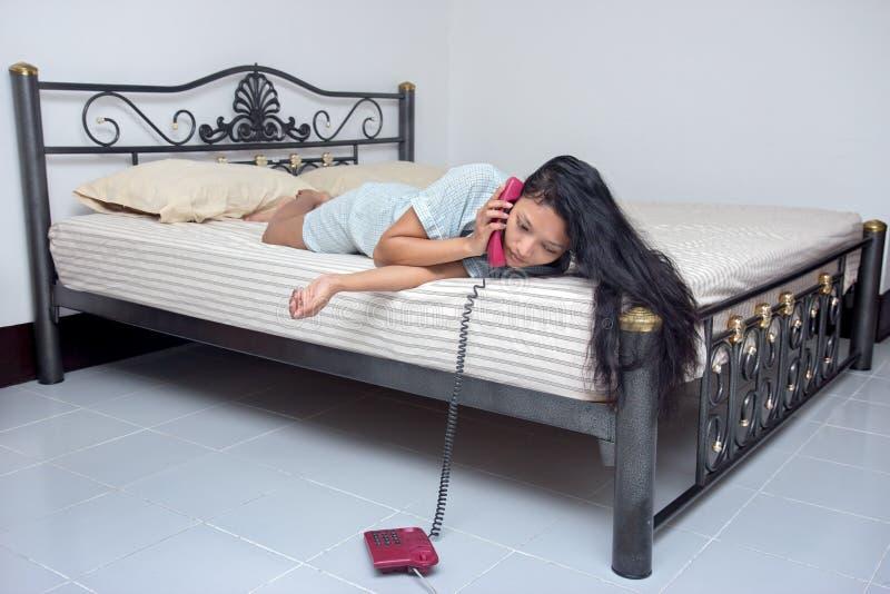 Femme se situant dans le lit et appelant du téléphone image stock