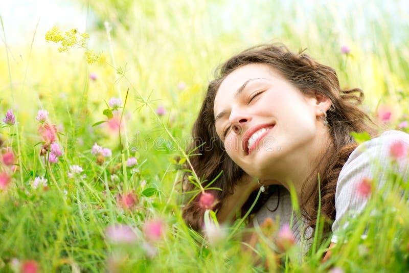 Femme se situant dans le pré des fleurs photographie stock libre de droits