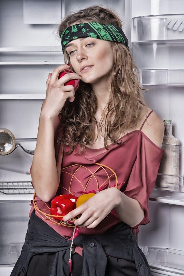 Femme se tenant à côté du réfrigérateur vide Fille dans la bande principale hippie tenant la cuvette avec des légumes Pomme modèl image stock