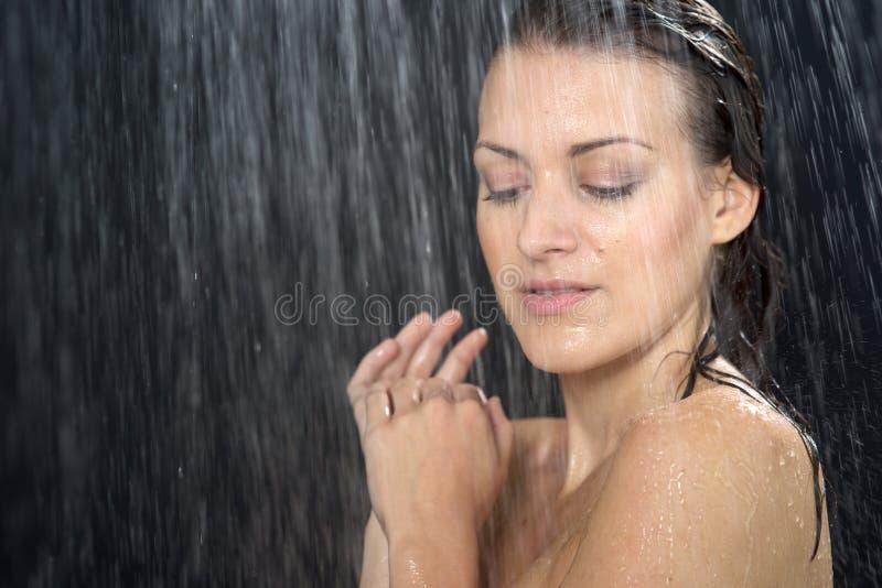 Femme se tenant à la douche photographie stock