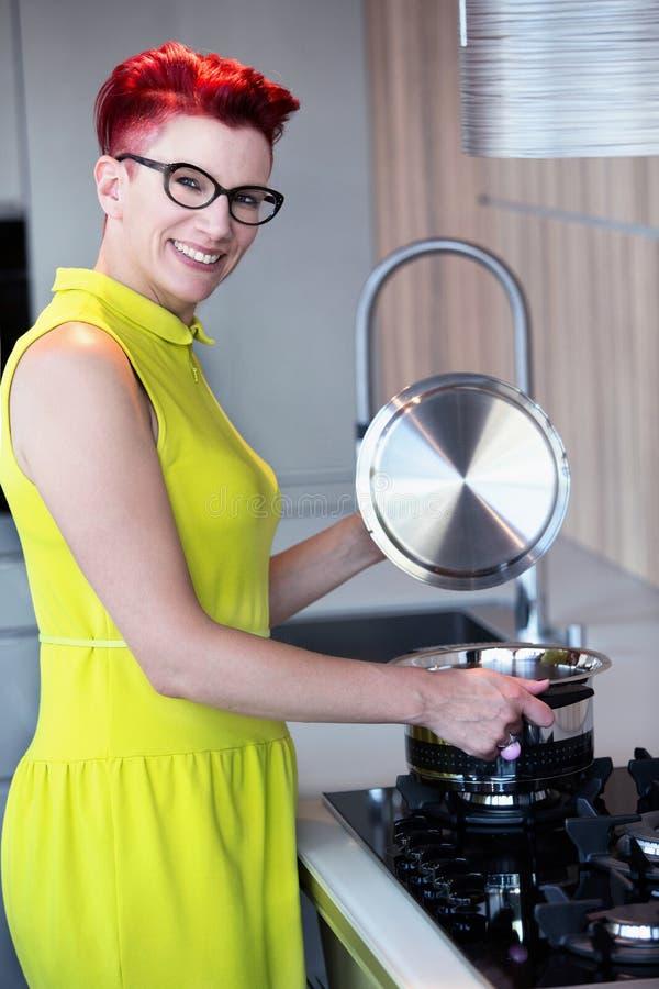 Femme se tenant au fourneau dans la cuisine image stock