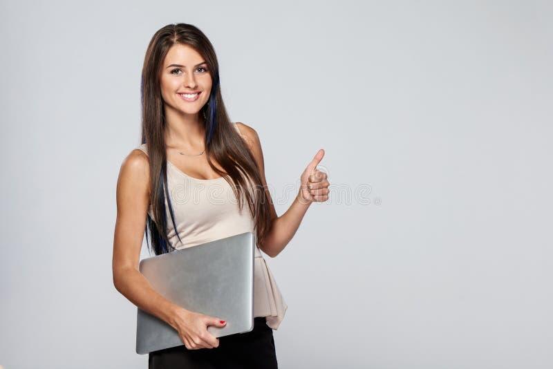 Femme se tenant avec l'ordinateur portable fermé photo libre de droits