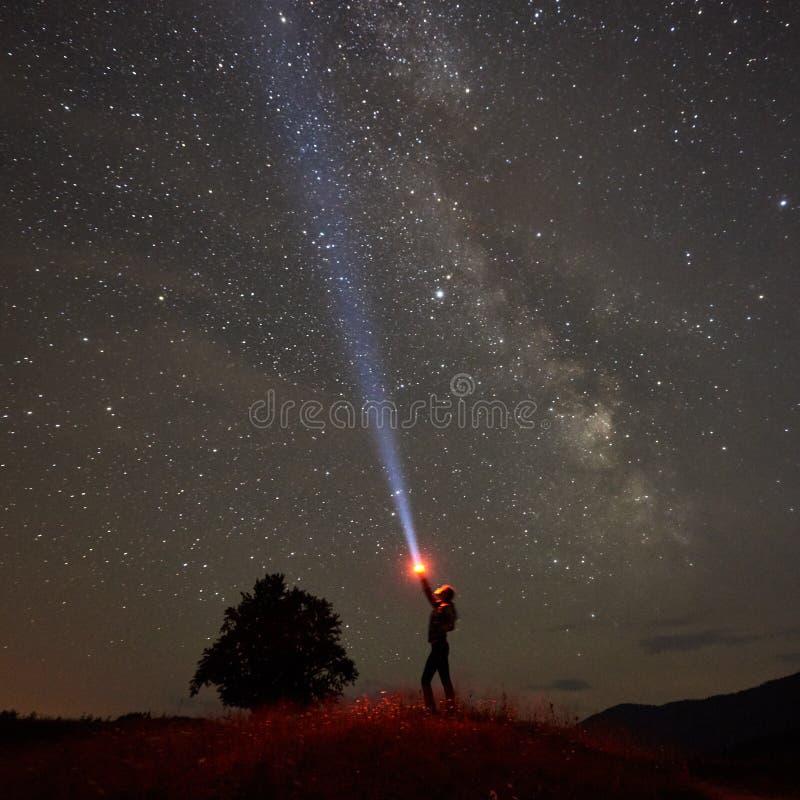 Femme se tenant contre le ciel étoilé de nuit avec la manière laiteuse dans les montagnes avec la lampe-torche dans sa main photo stock