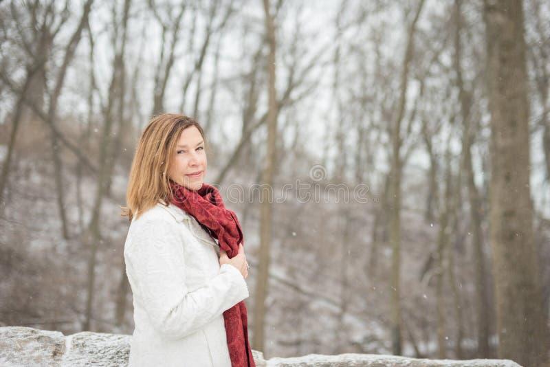 Femme se tenant dans la forêt en hiver avec l'écharpe rouge en tant que neige fraîche photo stock