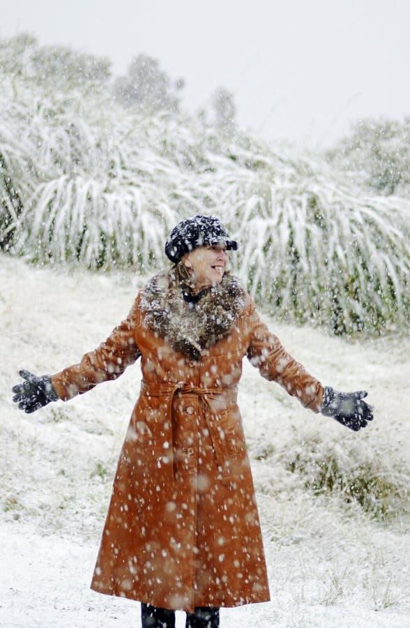 Femme se tenant dans la neige en admiration devant la scène d'hiver images stock