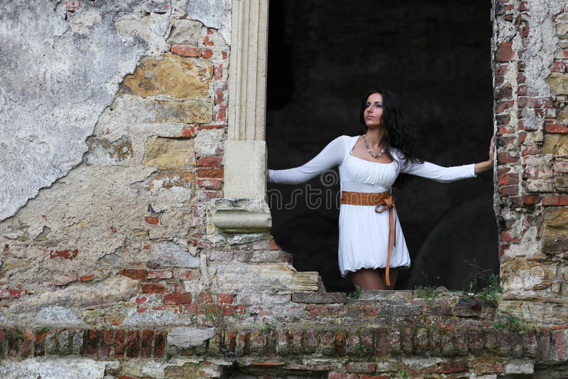 Femme se tenant dans le châssis de fenêtre image stock
