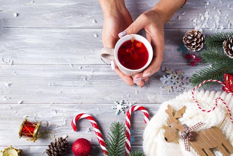 Femme se tenant dans le thé chaud de Noël de mains avec la sucrerie image stock