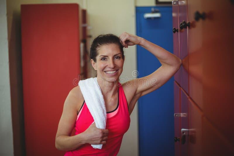 Femme se tenant dans le vestiaire de gymnase après séance d'entraînement photo stock