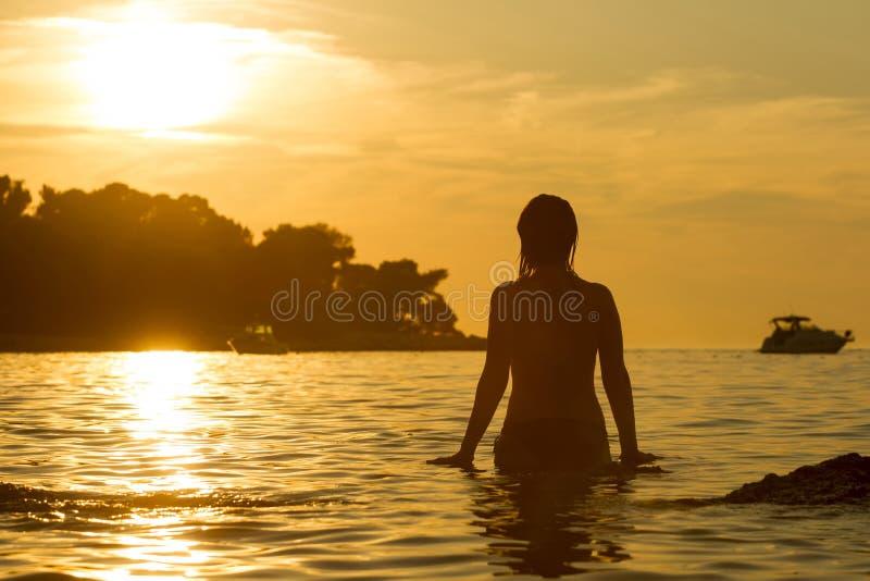Femme se tenant dans peu profond au coucher du soleil image libre de droits