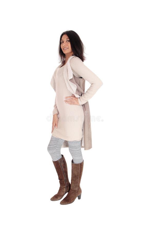 Femme se tenant dans une robe, un manteau et des bottes images libres de droits