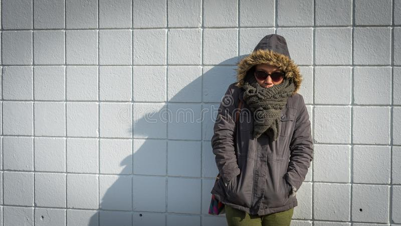 Femme se tenant devant le mur blanc de tuile photos libres de droits