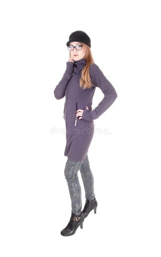Femme se tenant en chapeau et verres de manteau d'hiver photos stock