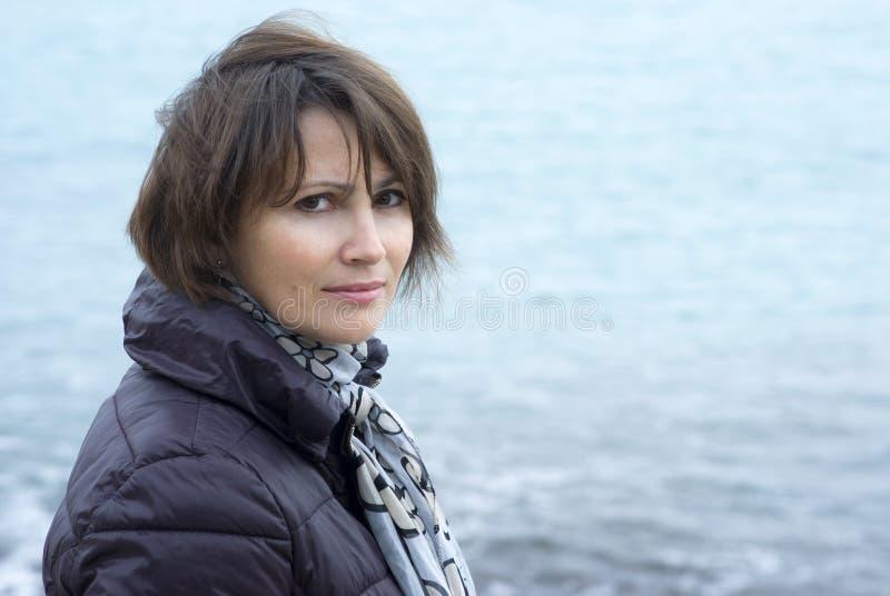 Femme se tenant en conditions venteuses devant la mer photos stock