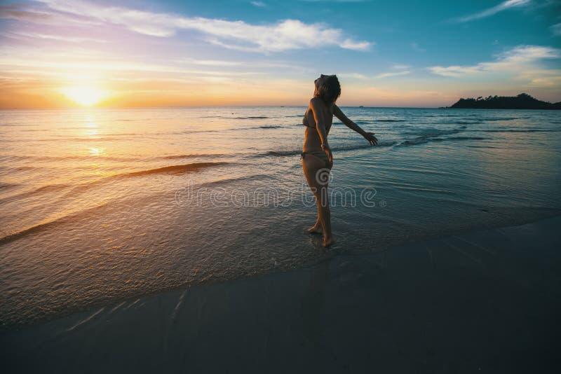 Femme se tenant sur la plage pendant le beau coucher du soleil détendez photo libre de droits