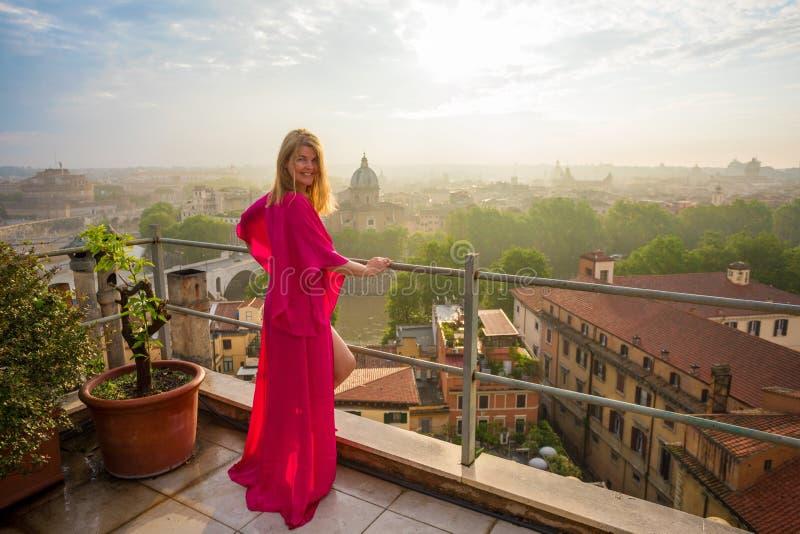 Femme se tenant sur la terrasse et la ville de négligence dans le début de la matinée photo libre de droits
