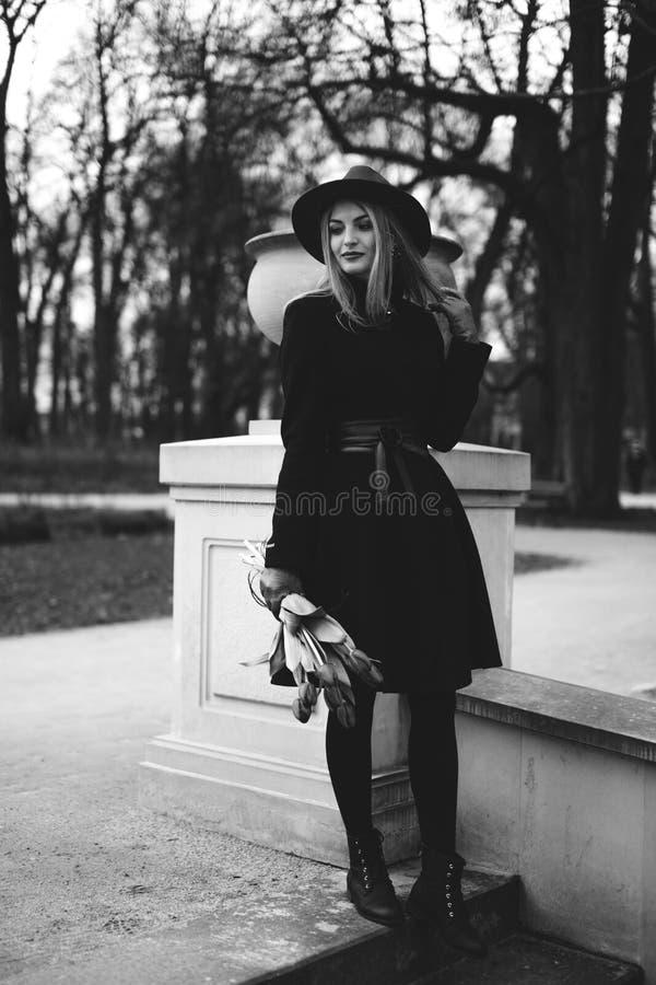 Femme se tenant sur le fond de parc avec des fleurs photographie stock