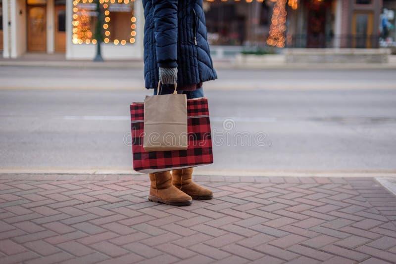 Femme se tenant sur le trottoir tenant des achats de Noël de sacs photographie stock