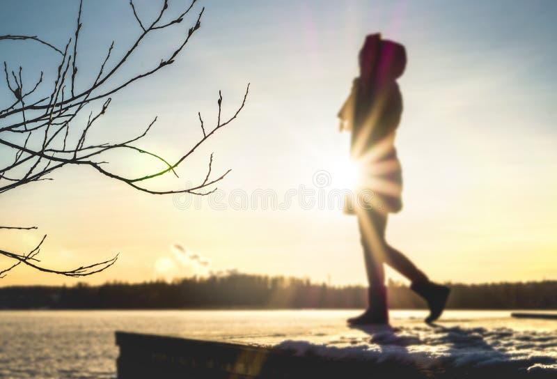Femme se tenant sur un pilier à côté d'un lac en hiver au coucher du soleil photographie stock libre de droits