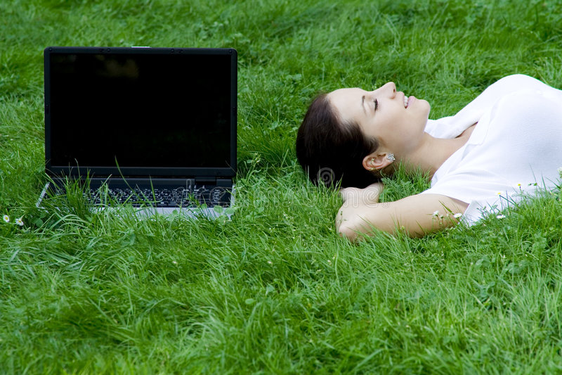 Femme se trouvant sur l'herbe avec l'ordinateur portatif image stock