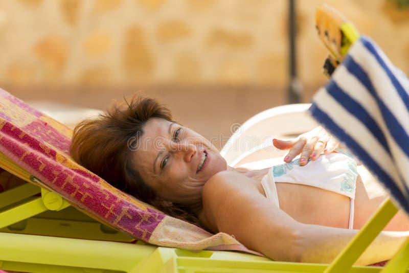 Femme se trouvant sur la chaise en été photo stock