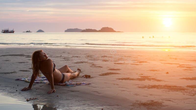 Femme se trouvant sur la plage dans le coucher de soleil photographie stock