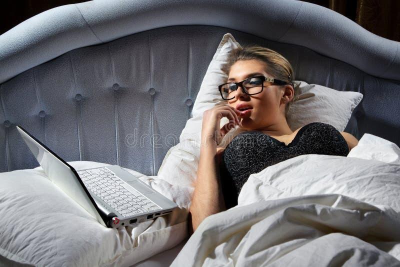 Femme se trouvant sur le bâti avec un ordinateur portatif photographie stock libre de droits