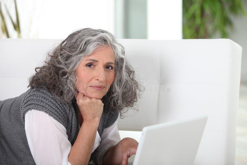 Femme se trouvant sur le divan images stock