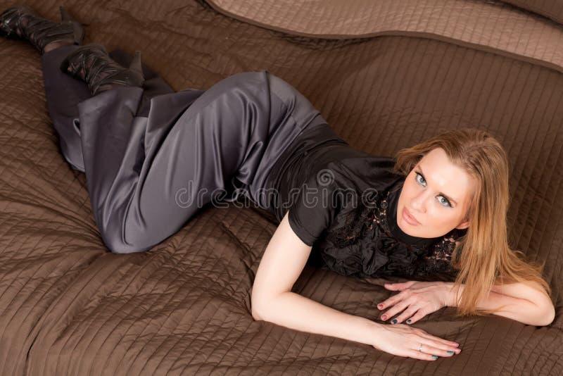 Femme se trouvant sur le divan photo stock