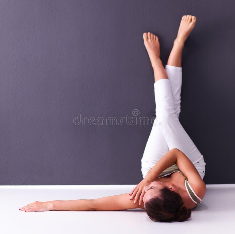 Femme se trouvant sur le plancher avec des jambes  images stock