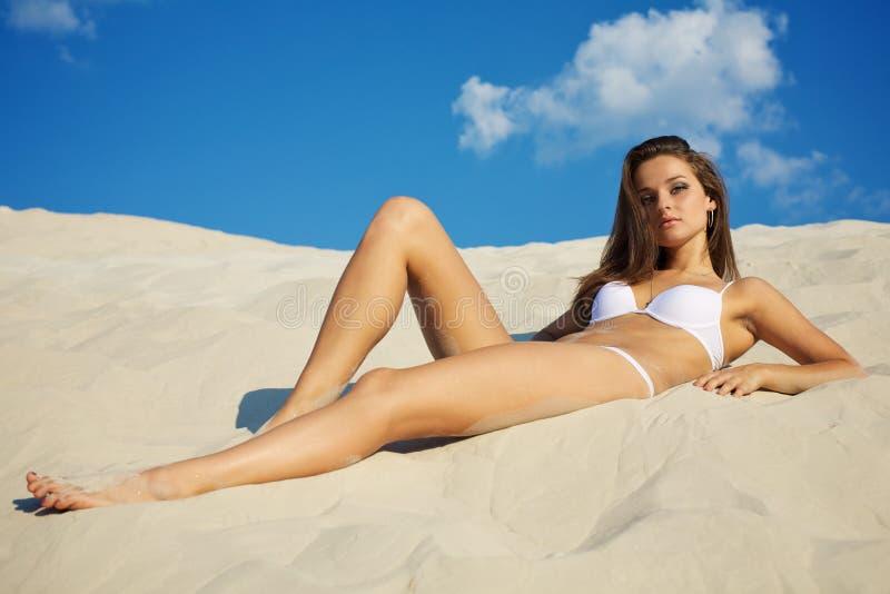 Femme se trouvant sur le sable photo stock
