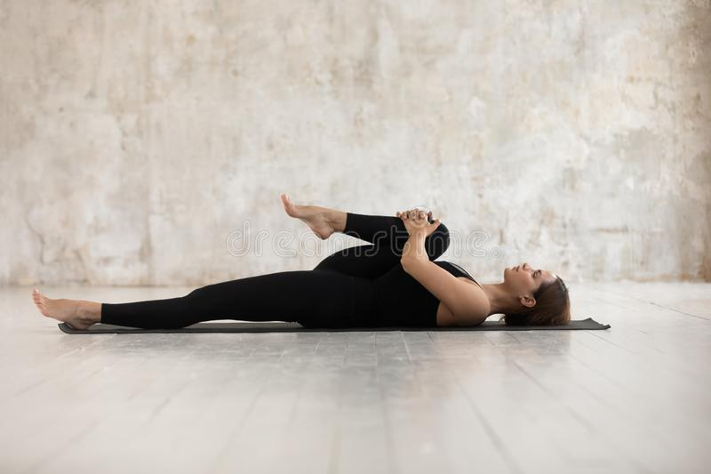 Femme se trouvant sur le tapis faisant de demi genoux à la pose de coffre photographie stock libre de droits