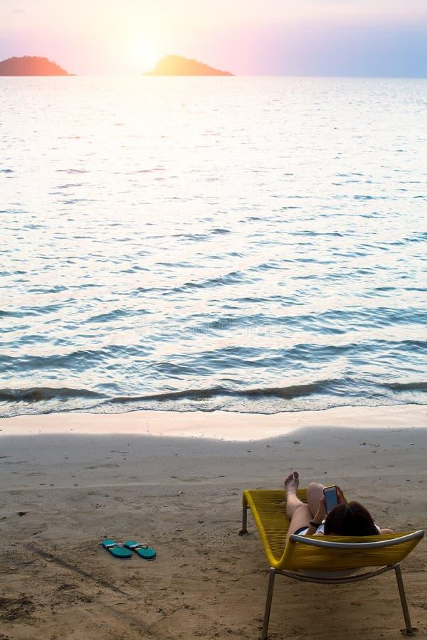 Femme se trouvant sur un canapé du soleil avec un smartphone sur la plage de mer photo stock