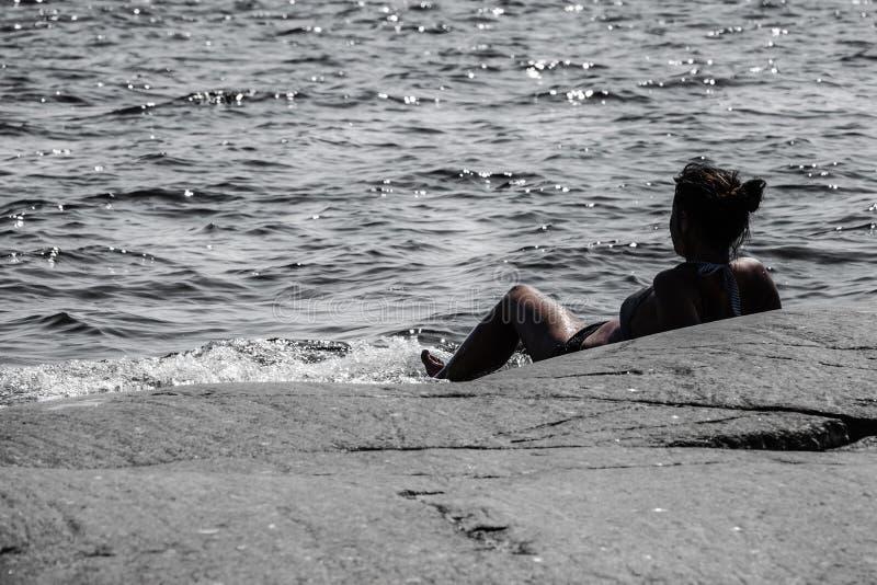 Femme se trouvant sur une roche dans l'océan regardant l'horizon photo libre de droits