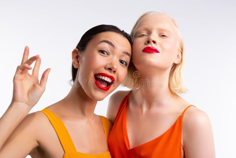 Femme semblant dr?le tout en passant le temps avec l'ami blond image libre de droits
