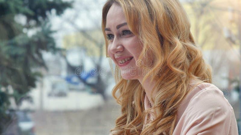 Femme semblant heureuse tout en parlant à son ami photographie stock libre de droits