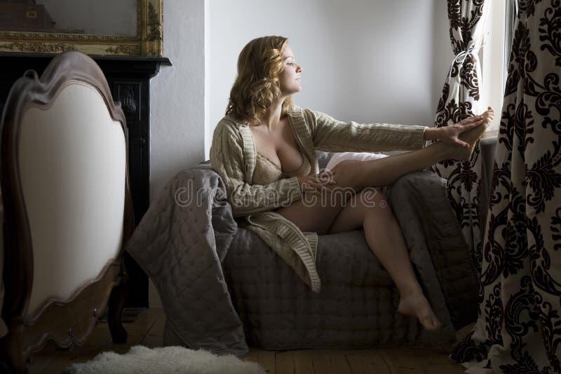 Femme semi habillée s'asseyant par la fenêtre à la maison photo stock