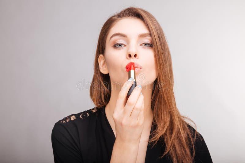Femme sensuelle à l'aide et démontrant du rouge à lèvres rouge sur ses lèvres photographie stock