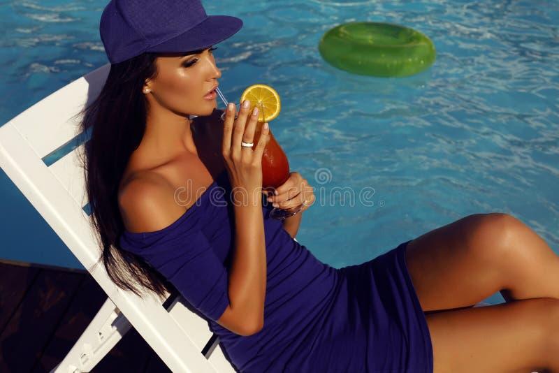 Femme sensuelle avec le cocktail potable de cheveux foncés près de la piscine photo libre de droits