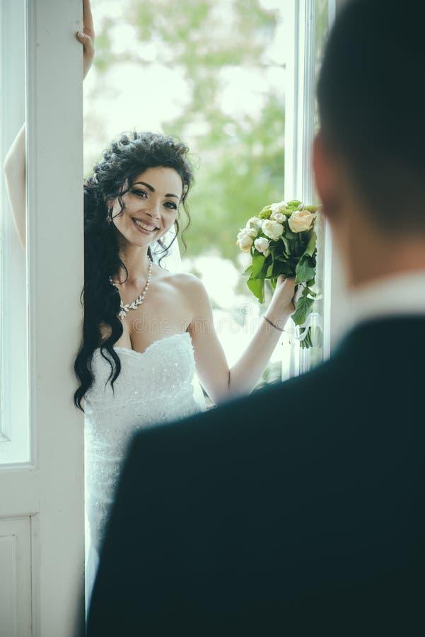 Femme sensuelle avec le maquillage et la coiffure nuptiales Sourire heureux de jeune mariée à toiletter Femme et homme le jour du images stock