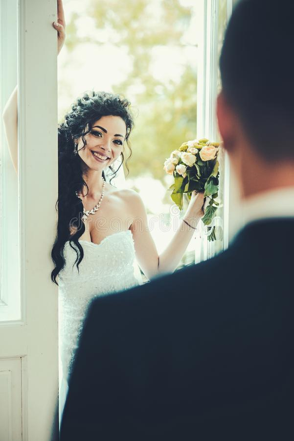 Femme sensuelle avec le maquillage et la coiffure nuptiales Sourire heureux de jeune mariée à toiletter Femme et homme le jour du photographie stock