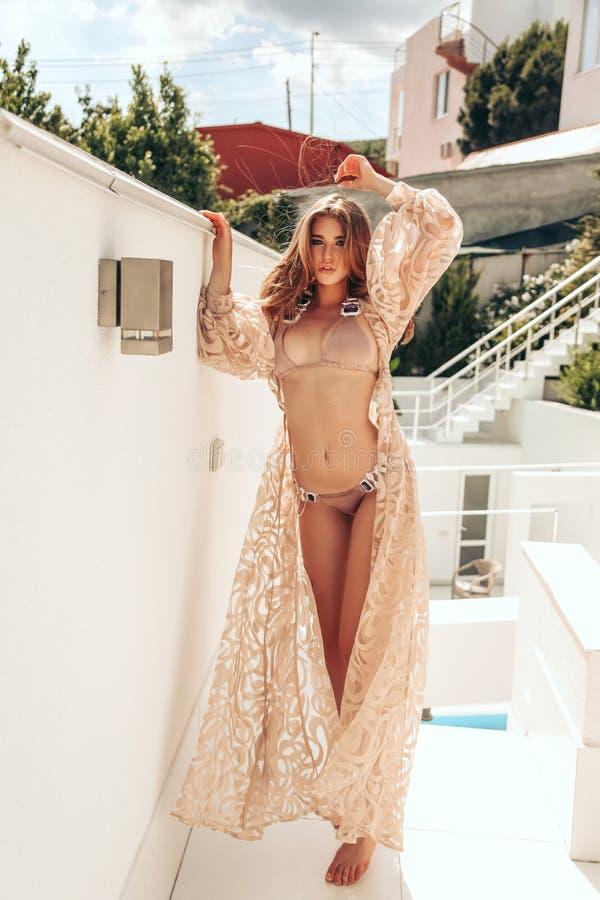 Femme sensuelle avec les cheveux blonds dans le costume de natation élégant posant près de la piscine photos stock